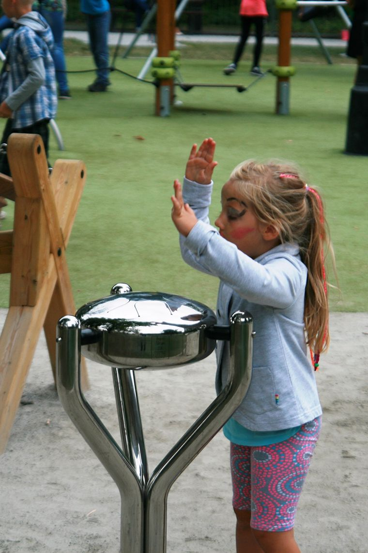 Young girl playing a silver steel tongue drum in a playground
