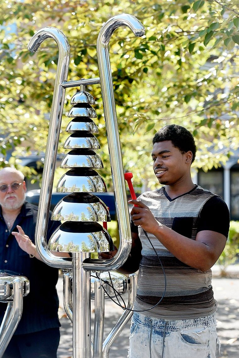 Black man playing a tall silver bell tree in the park
