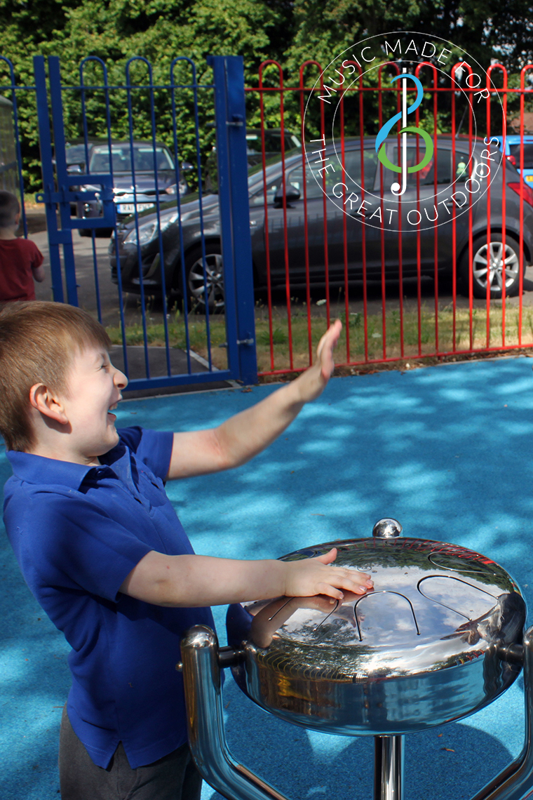 boy playing silver tongue drum in a school playground
