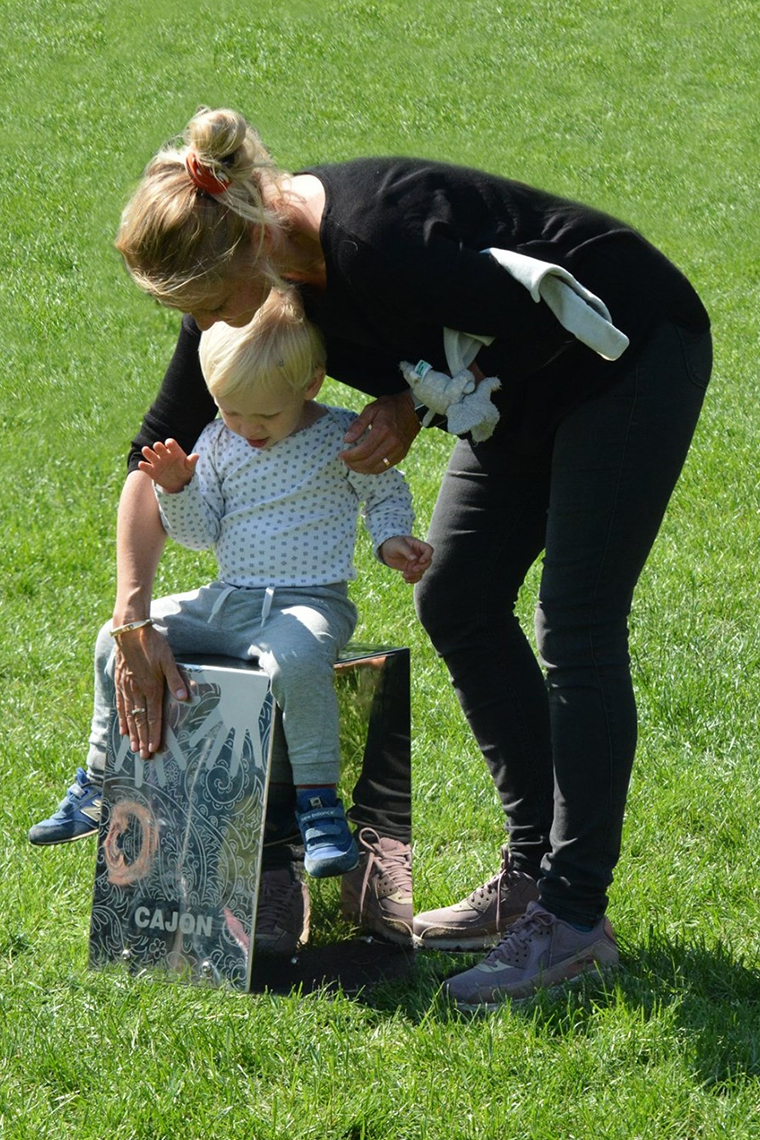 Mother standing over a child sat on a stainless steel outdoor cajon drum in a music park