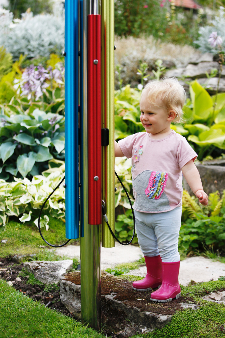 little blonde boy playing an outdoor rainbow chime post in a musical playground