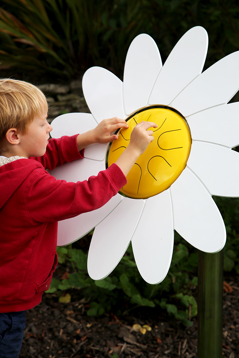 A young boy playing an outdoor musical drum in the shape and colours of a daisy