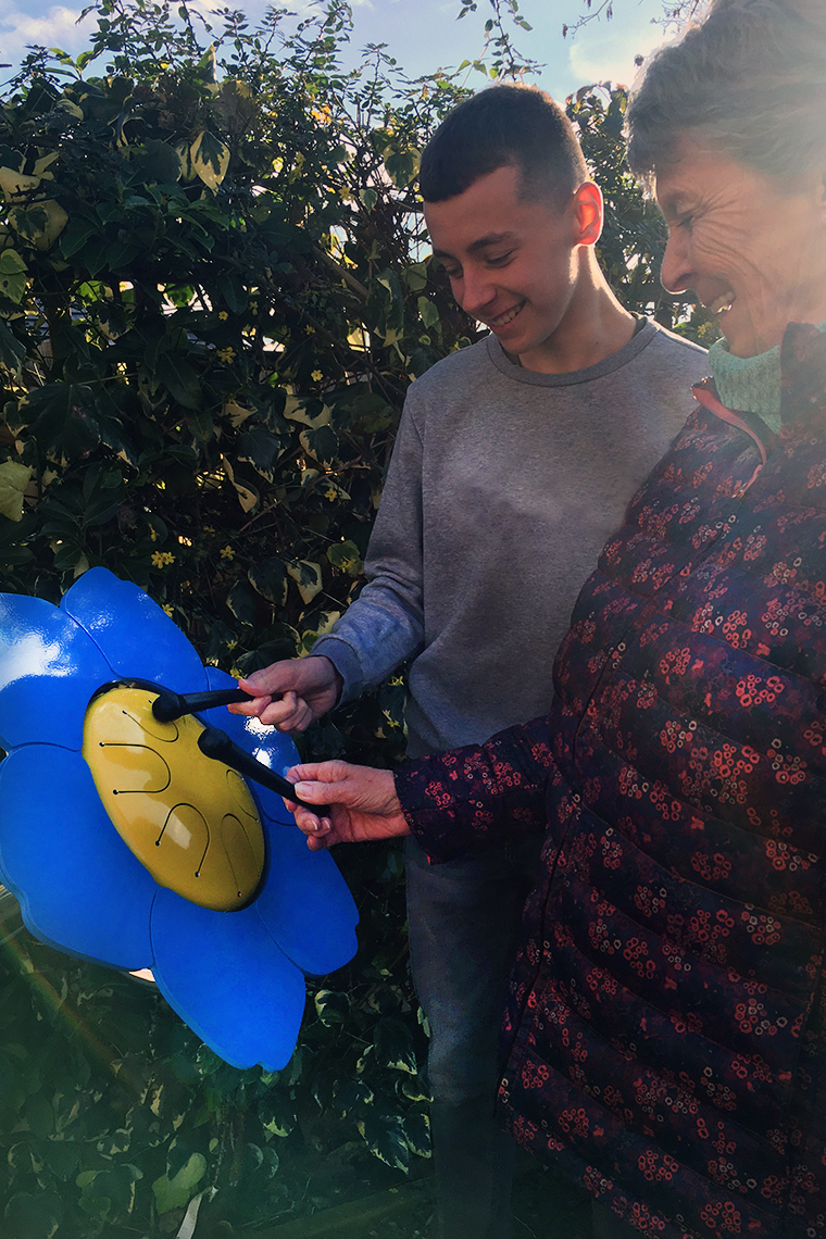 a grandmother and grandson playing on an outdoor drum shaped like a forget me not flower in a sensior care home