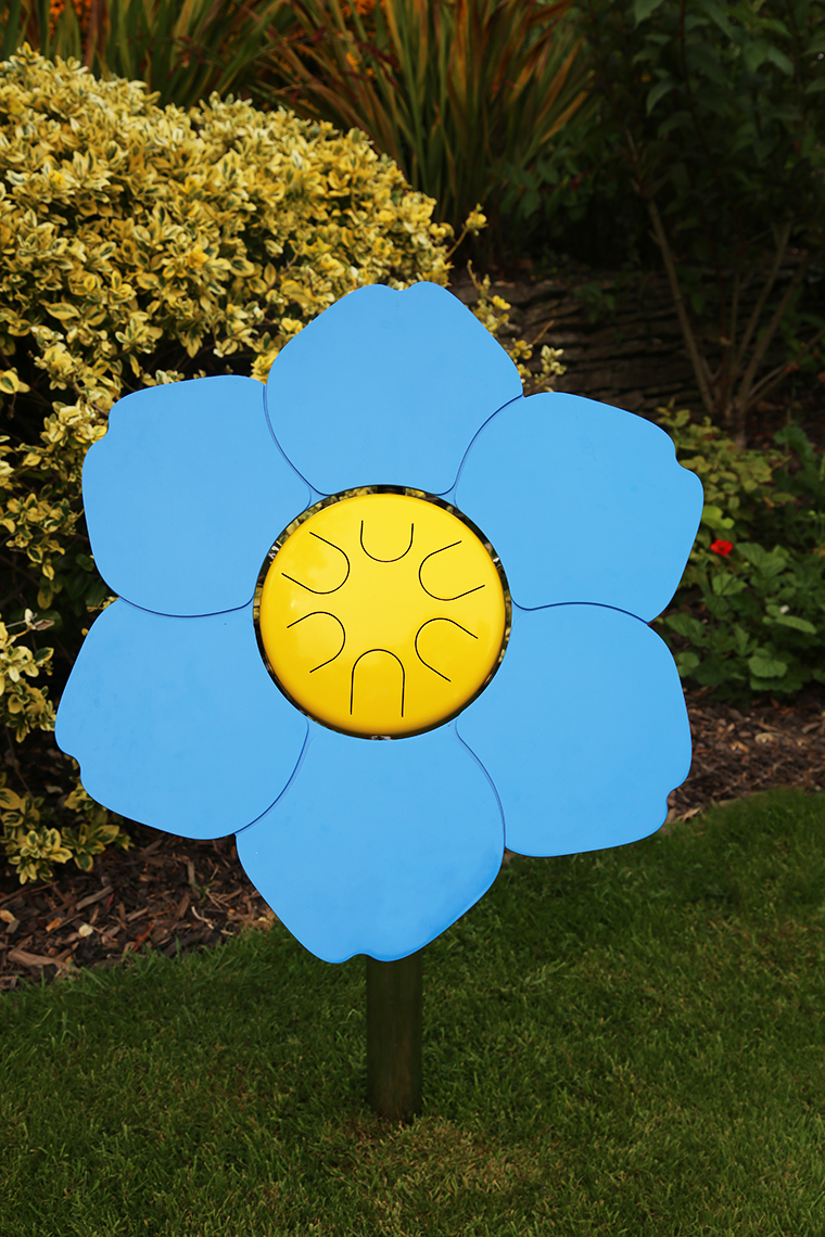 an outdoor musical drum in the shape and colours of a forget me not