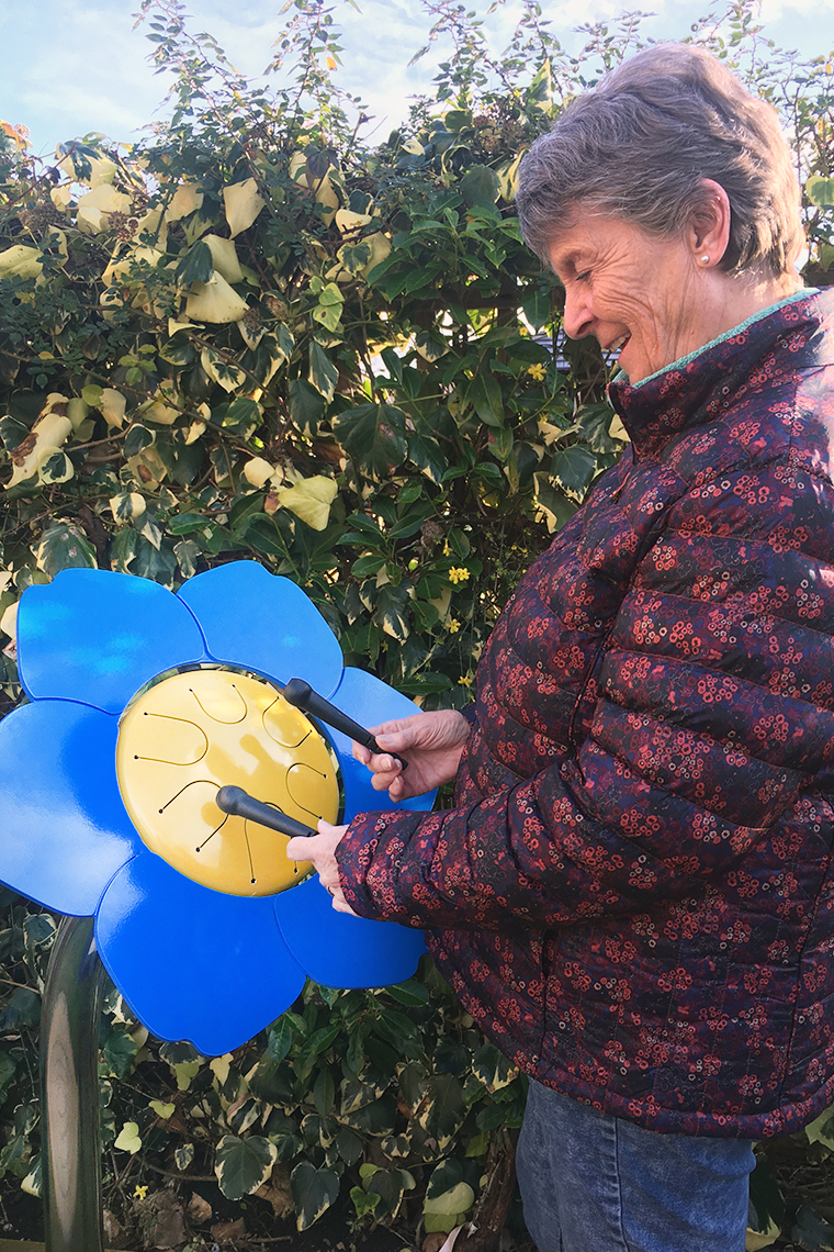 older lady playing a colorful outdoor drum shaped like a forget me not flower in a senior living center