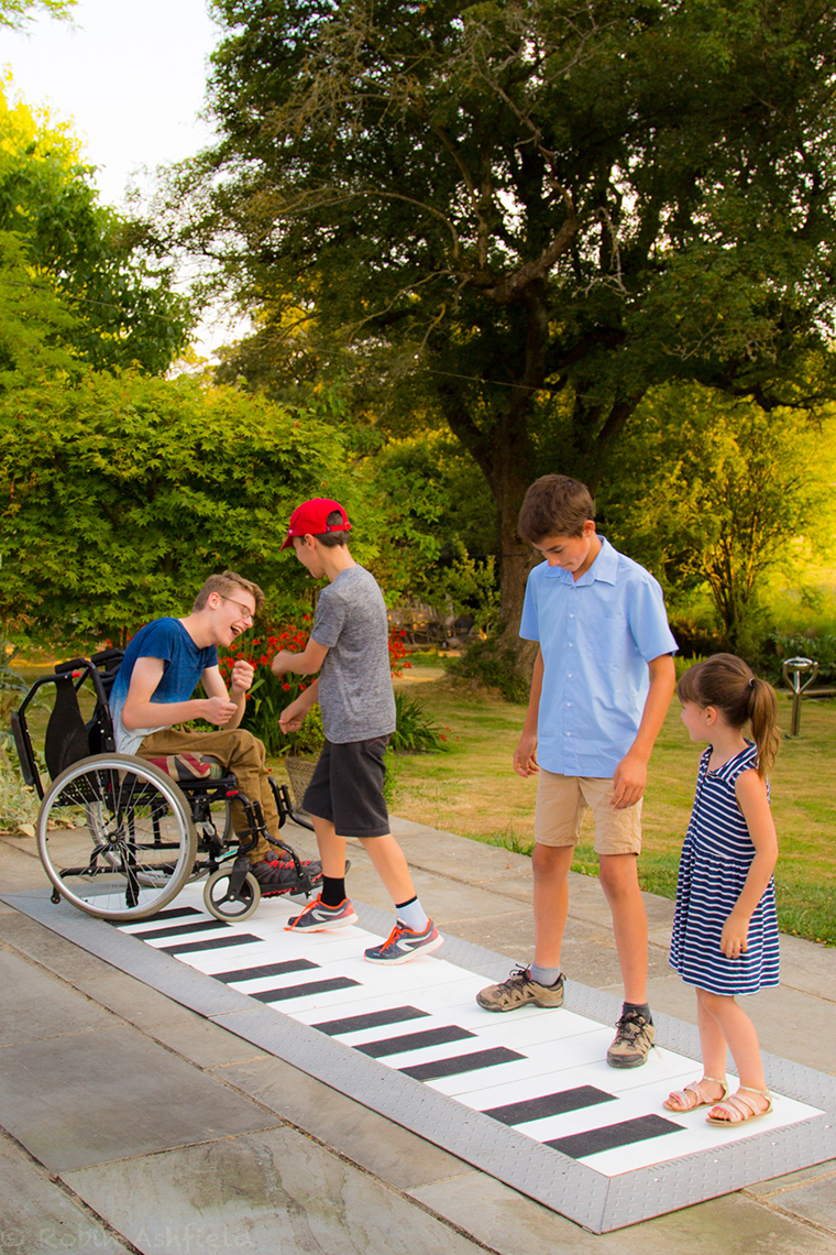 four children playing on a giant floor piano outdoors