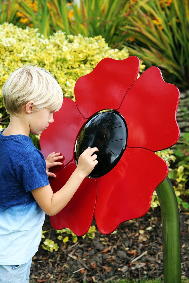 A young boy playing an outdoor musical drum in the shape and colours of a poppy