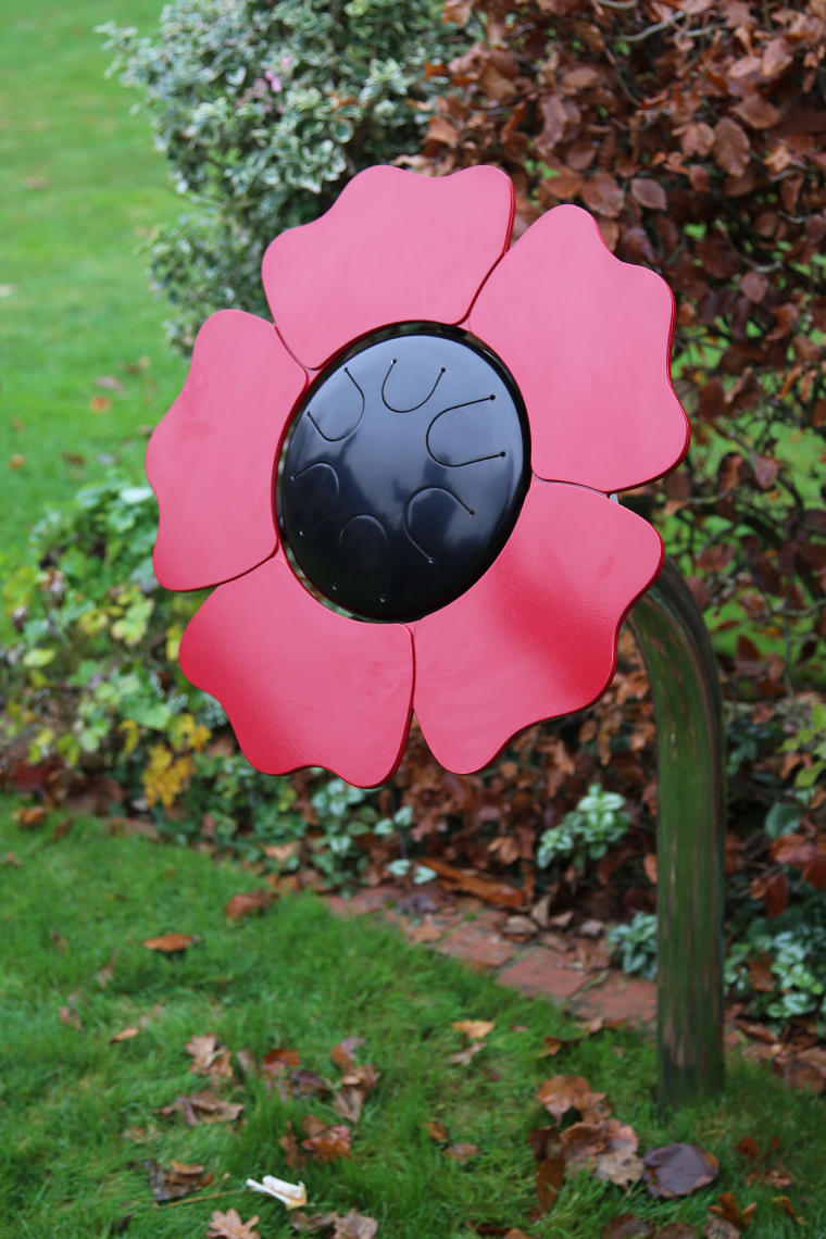 a black tongue drum with red petal surround to make an poppy shaped outdoor musical drum