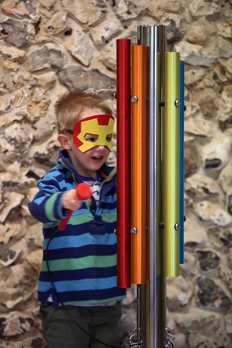 A little boy dressed as iron man playing an outdoor musical instrument made of a single stainless steel post and five bright coloured chimes attached