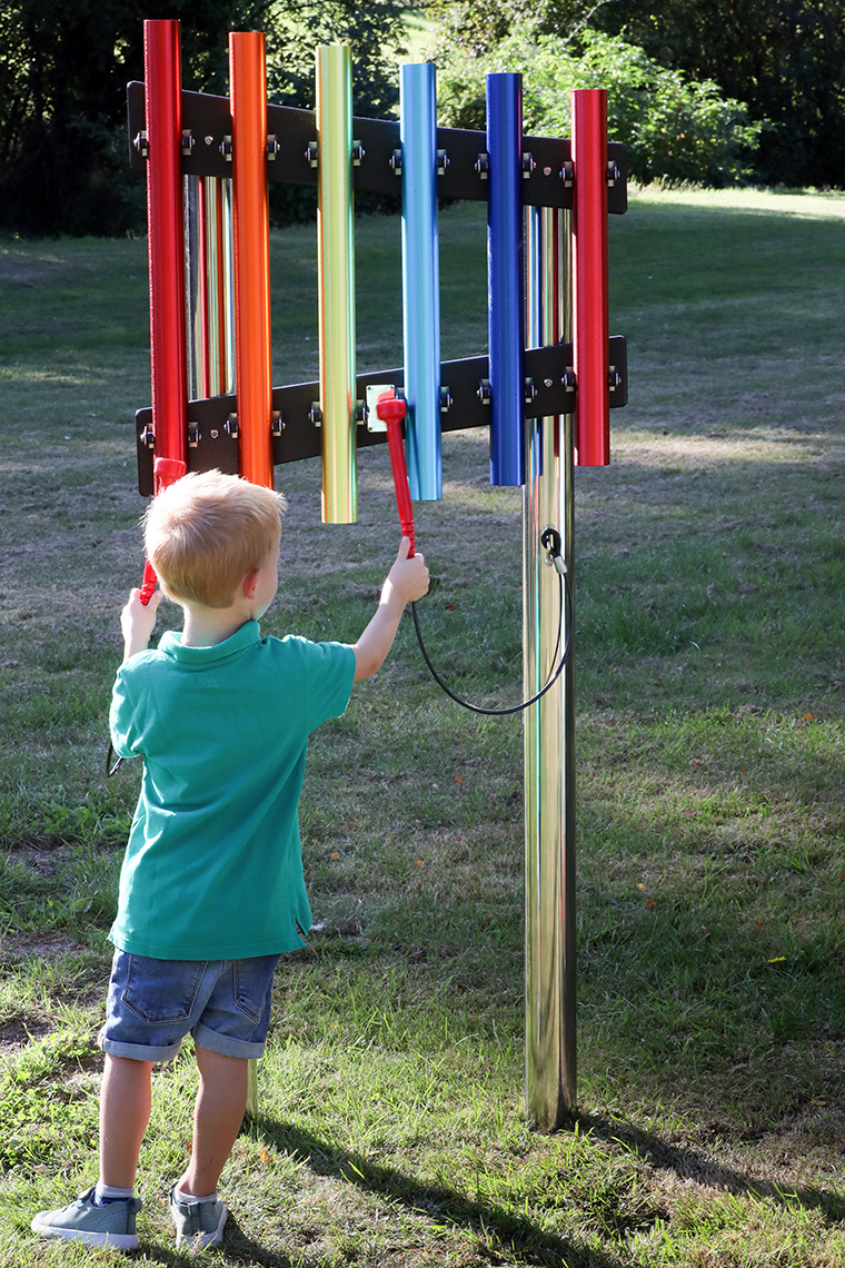 A little blonde boy playing on an outdoor musical instrument of five rainbow coloured chimes on a stainless steel post