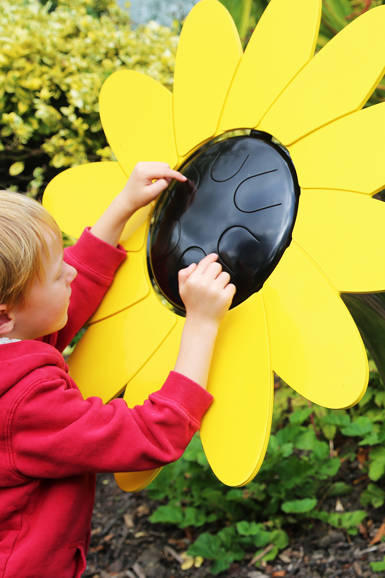 A young boy playing an outdoor musical drum in the shape and colours of a sunflower