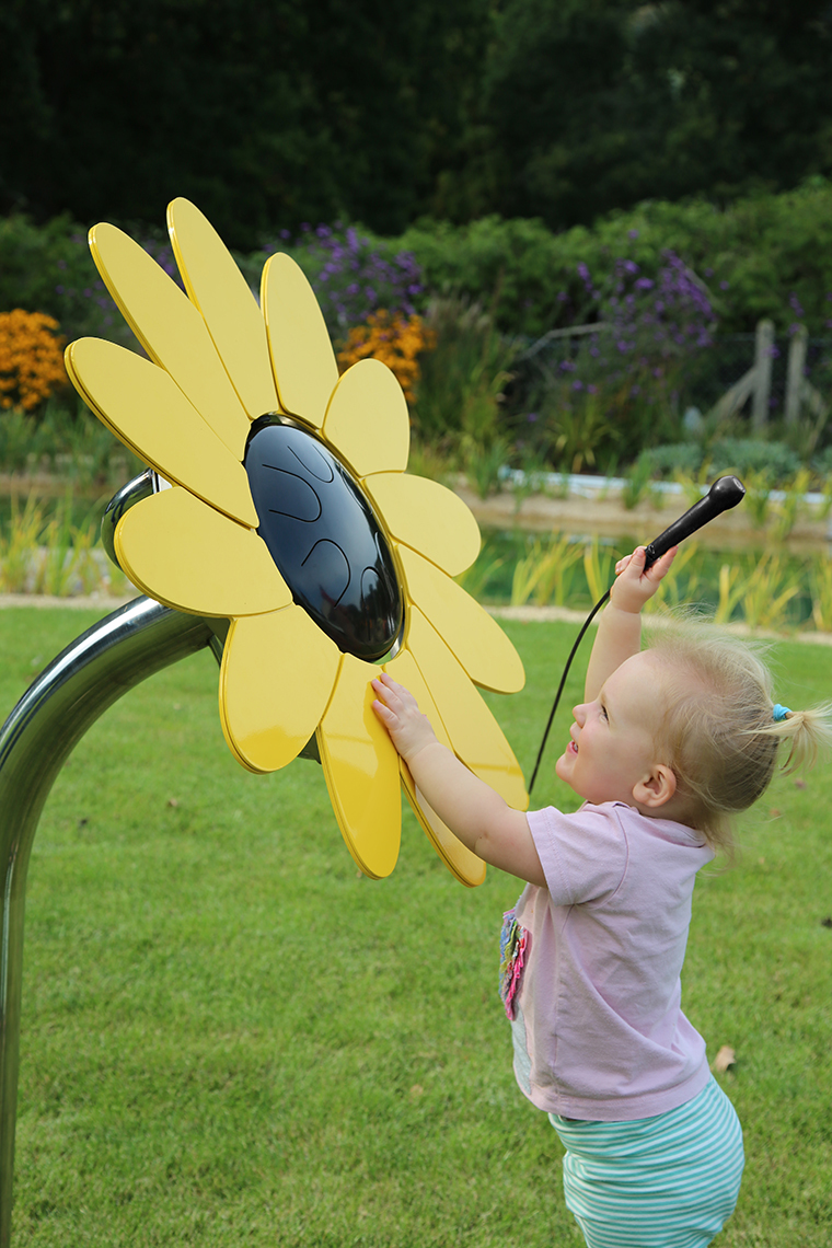 little girl reaching up playing an outdoor drum shaped like a sunflower
