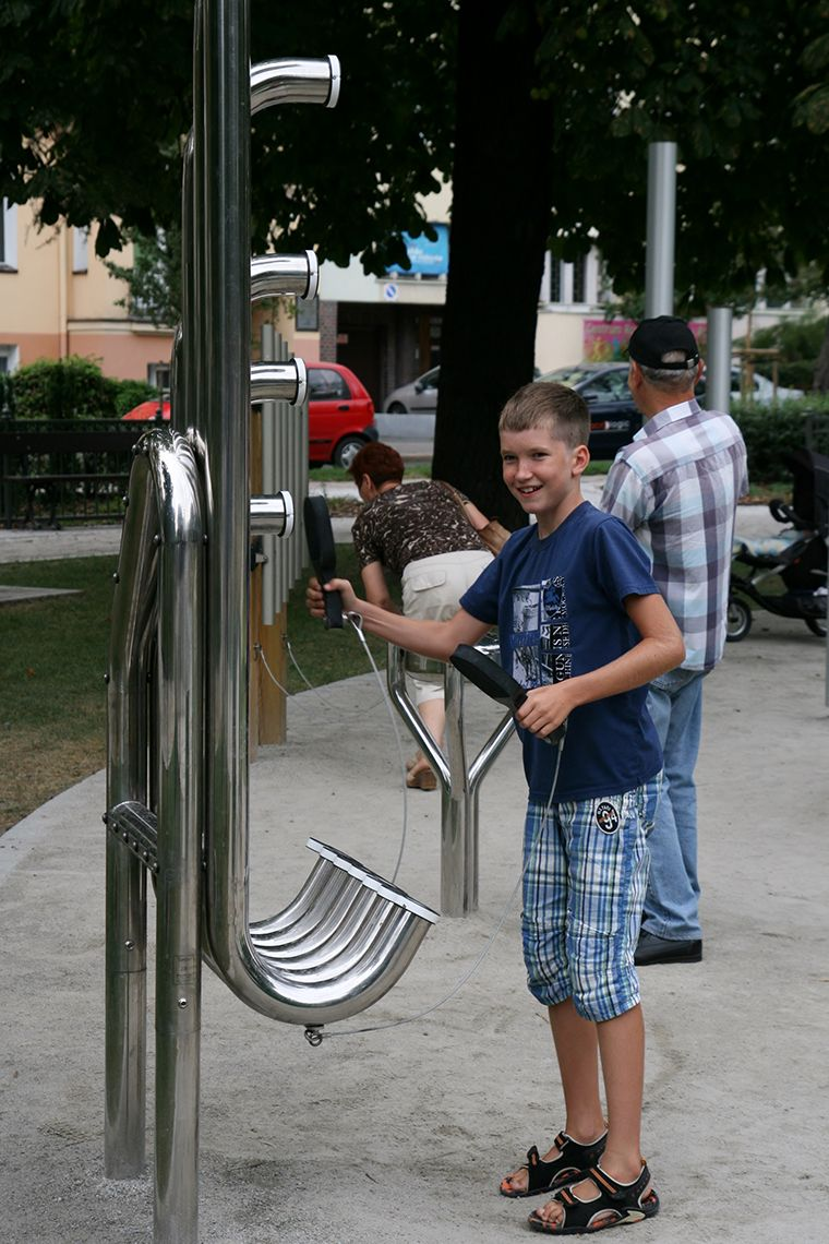 Teenage Boy Playing Stainless Steel aerophone outdoor musical instrument in park