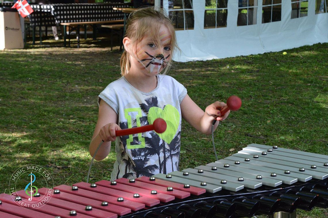 Young girl with her face painted playing a large outdoor xylophone in the park