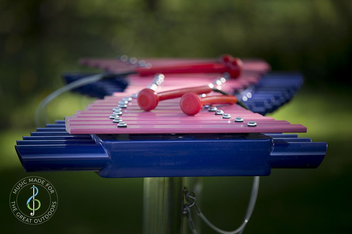 Close up image of large outdoor xylophone with pink grp notes and indigo blue abs resonators