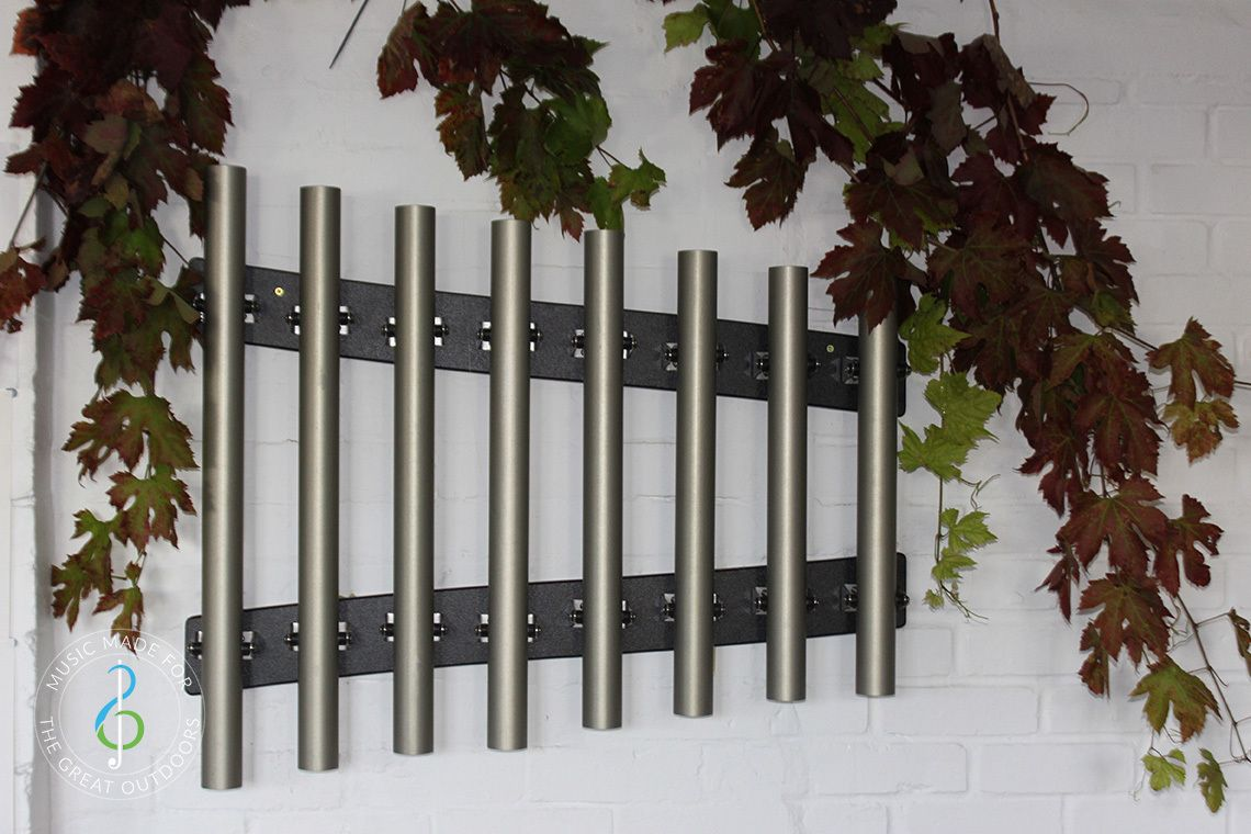 outdoor musical chimes mounted on a white wall covered in ivy