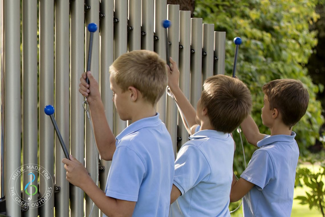 Close up image of three boys playing outdoor chimes in playground