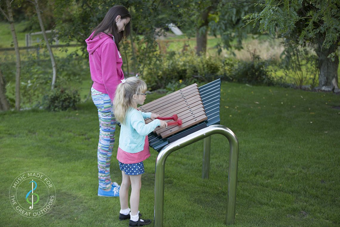 two girls in a park playing large outdoor marimba xylophone with wooden notes and stainless steel legs