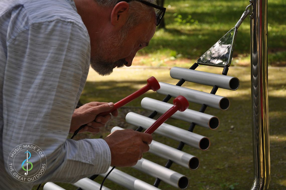 close up of elder man playing a xylophone in the park