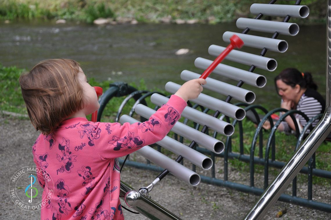 small girl playing large xylophone in a park