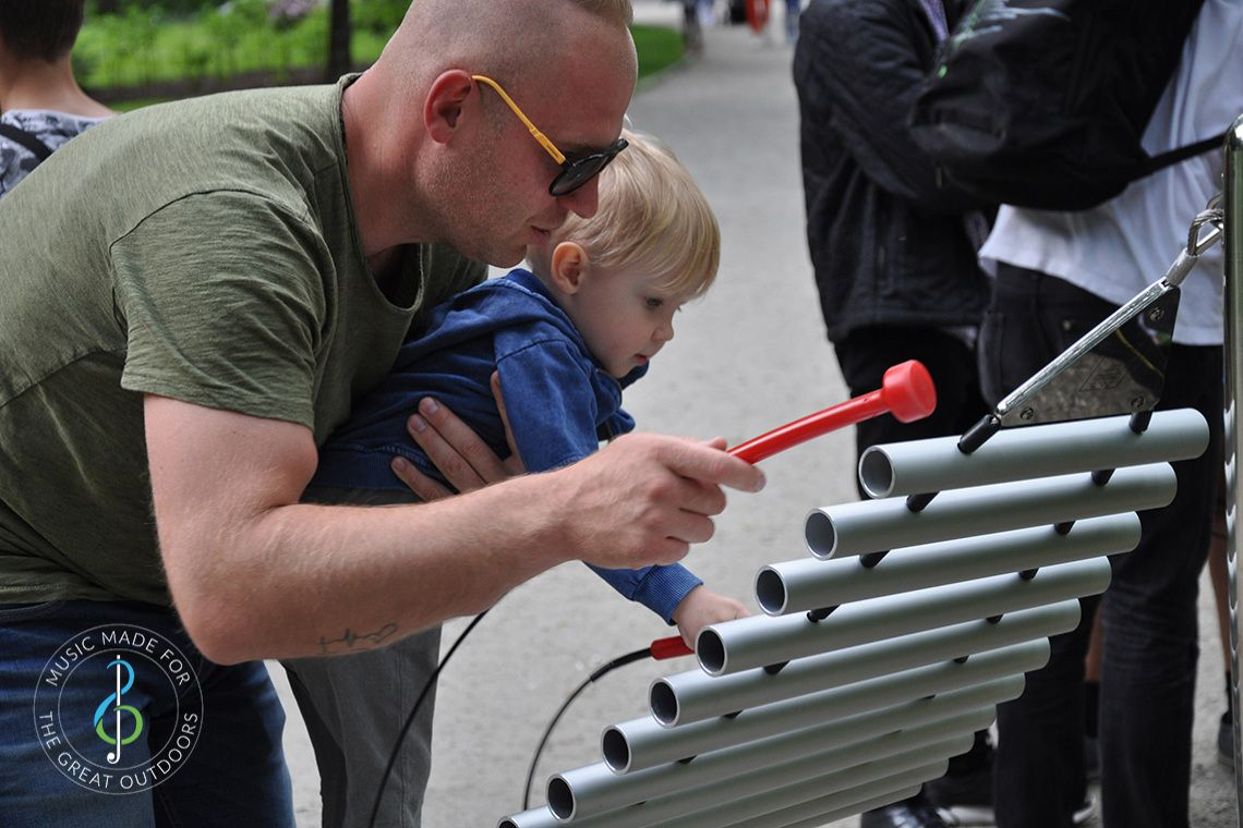 father holding a small child up and playing a large outdoor xylophone together in the park