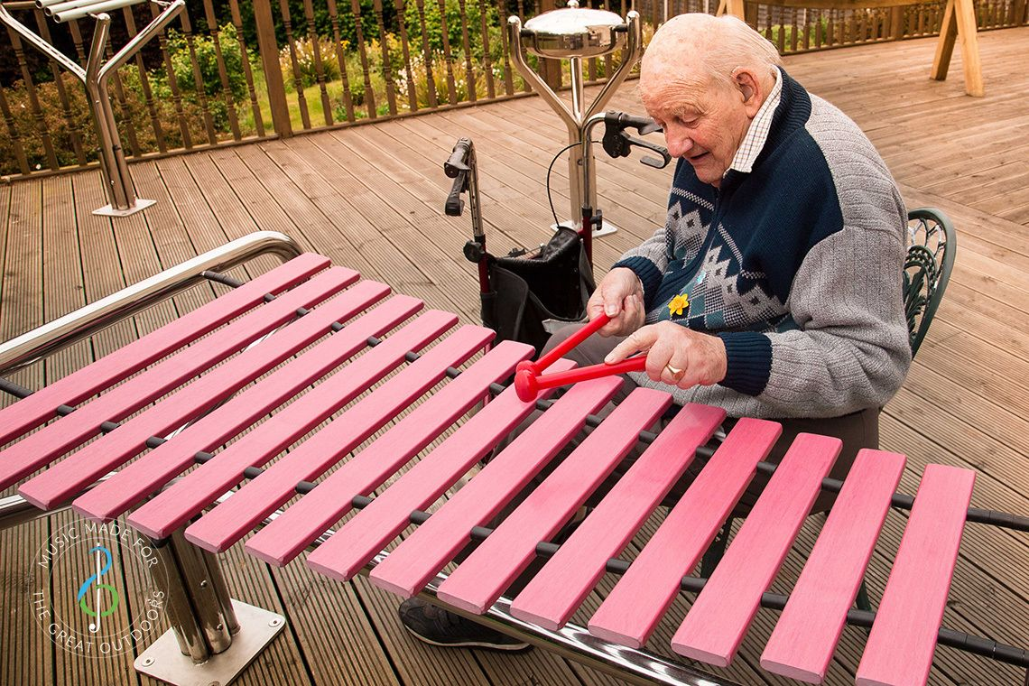 older man in wheelchair playing a large outdoor marimba in care home garden