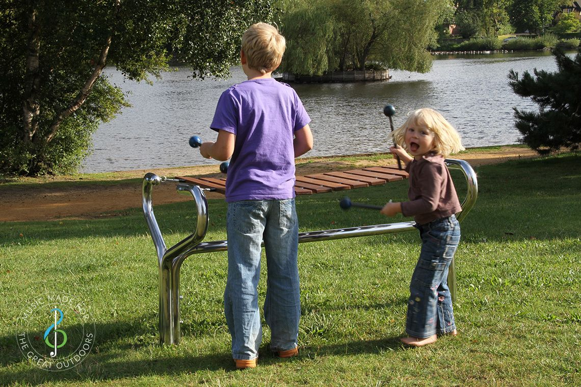 young boy and girl playing a large outdoor marimba by the side of a lake