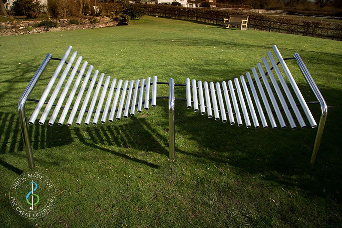 huge outdoor metallophone on grass with notes of anodised aluminium tubes, suspended by stainless steel cables and supported by a stainless steel frame.