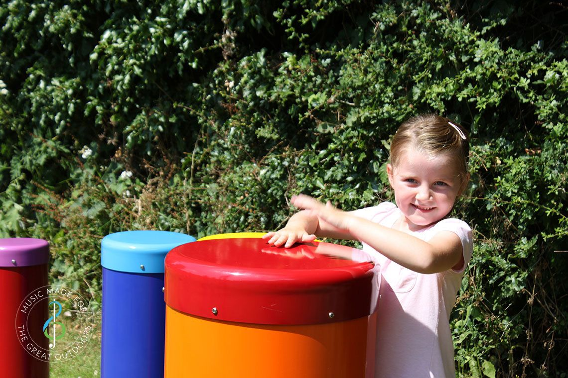 small girl playing large colourful drum in bright sunshine in a park