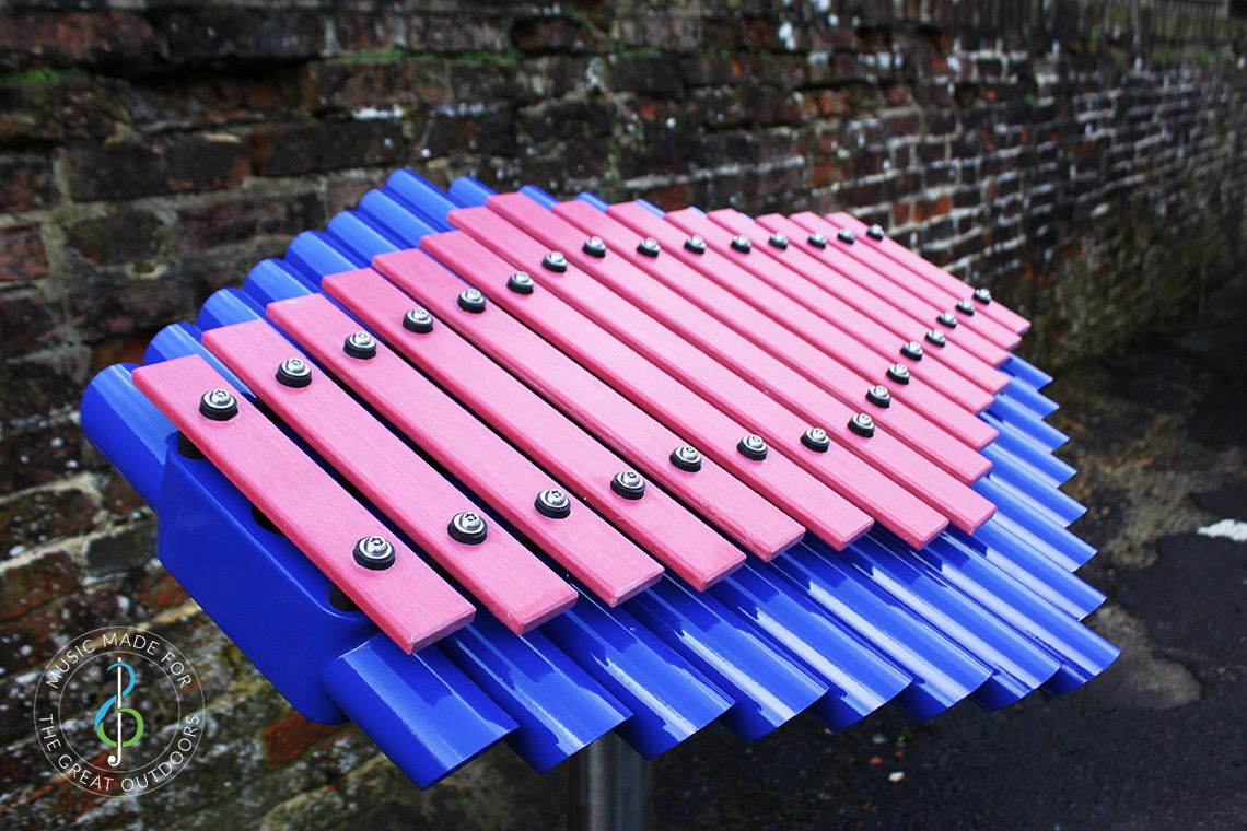 close up of outdoor xylophone with pink notes and blue resonators
