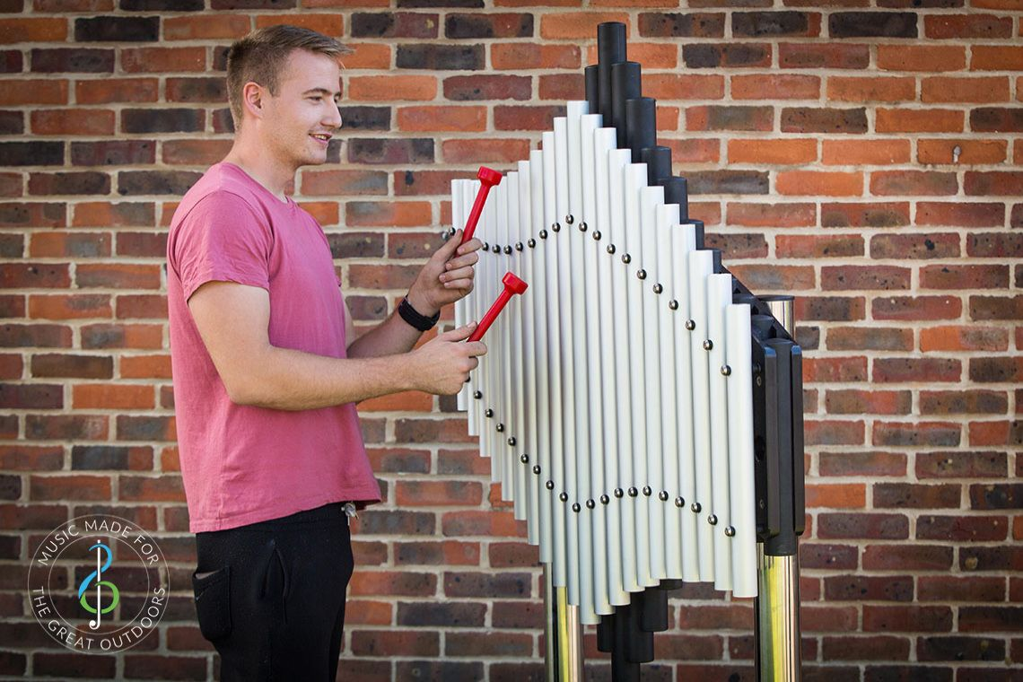young man playing large outdoor musical instrument with upright tubular notes mounted on black resonators