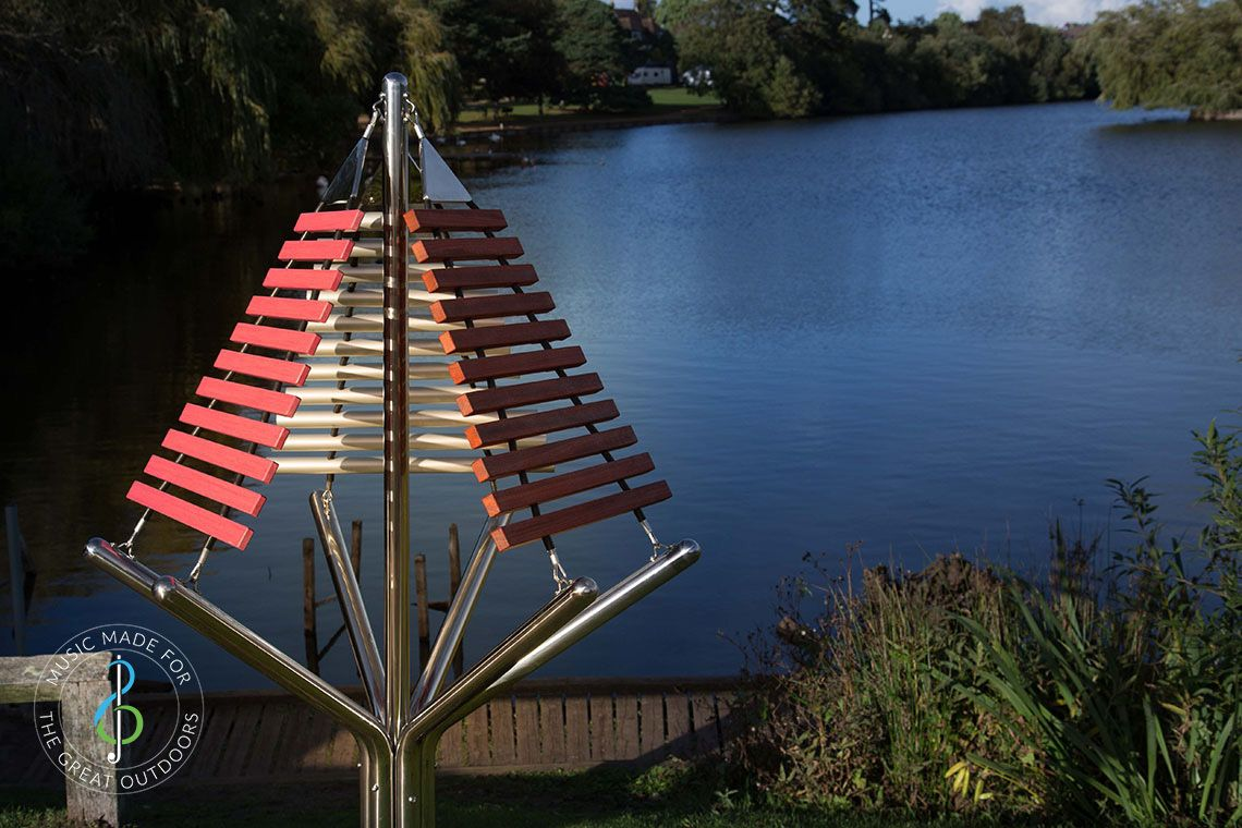 large outdoor musical instrument with one stainless steel post in ground with three vertical xylophones attached by lakeside