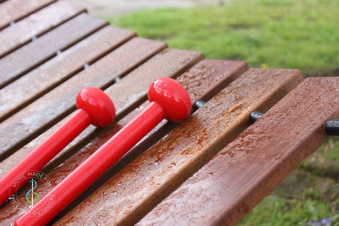 image of a Large Outdoor Playground Akadinda Xylophone with red beaters With Raindrops on the wooden notes