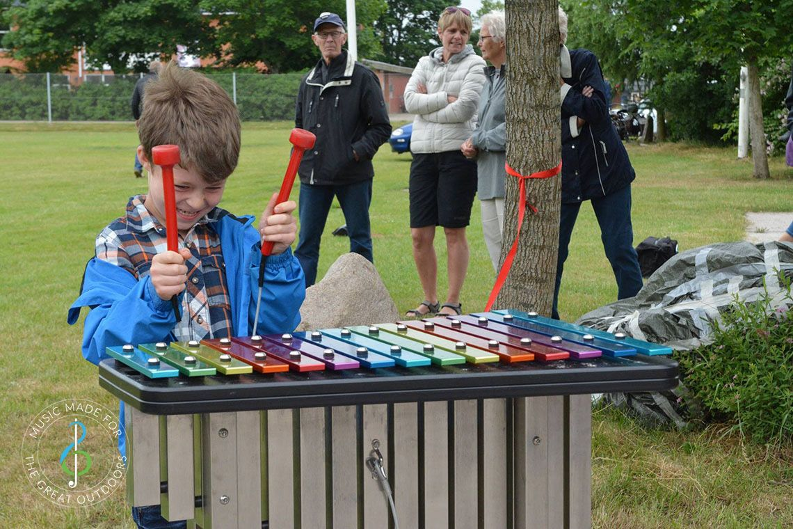 Boy Playing Rainbow Coloured Outdoor Xylophone in Park
