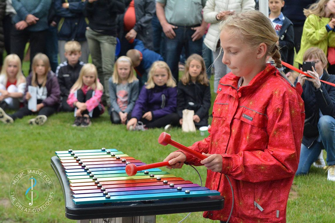 Girl Playing Rainbow Coloured Outdoor Xylophone with Audience