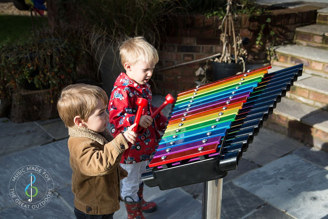 Two Young boys Playing Rainbow Coloured Xylophone Outdoors