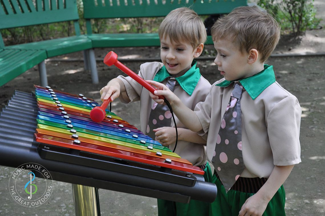 Two Young boys in Funny Ties Playing Rainbow Coloured Xylophone in Playground
