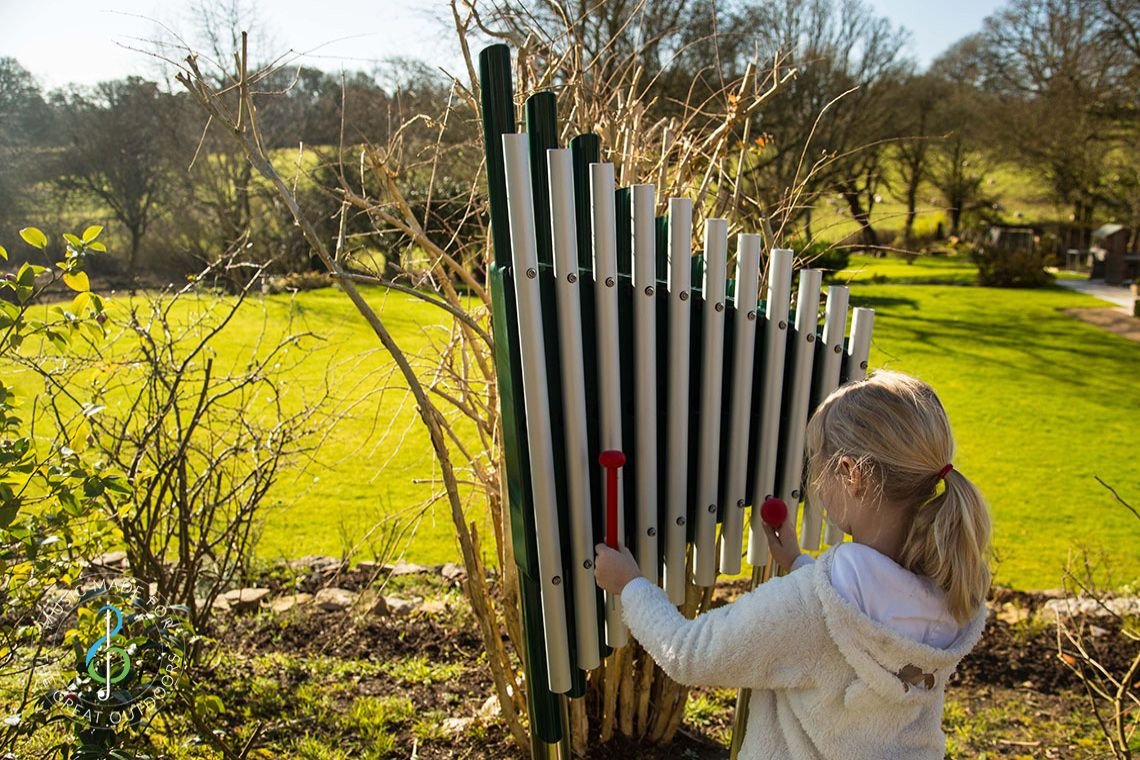 Young girl playing large vertical xylophone in the countryside
