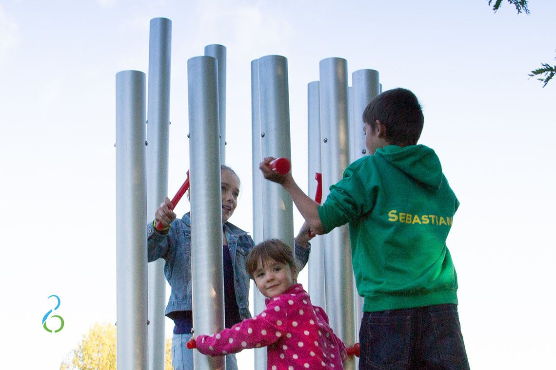 Three children hitting large silver coloured outdoor chimes with red beaters