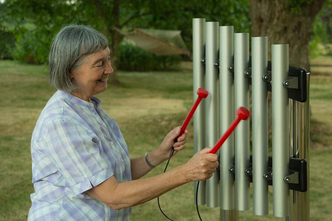 older lady smiling playing a set of outdoor musical chimes