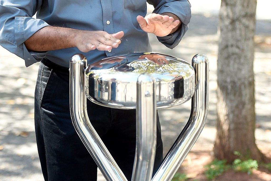 pair of male hands playing a stainless steel tongue drum