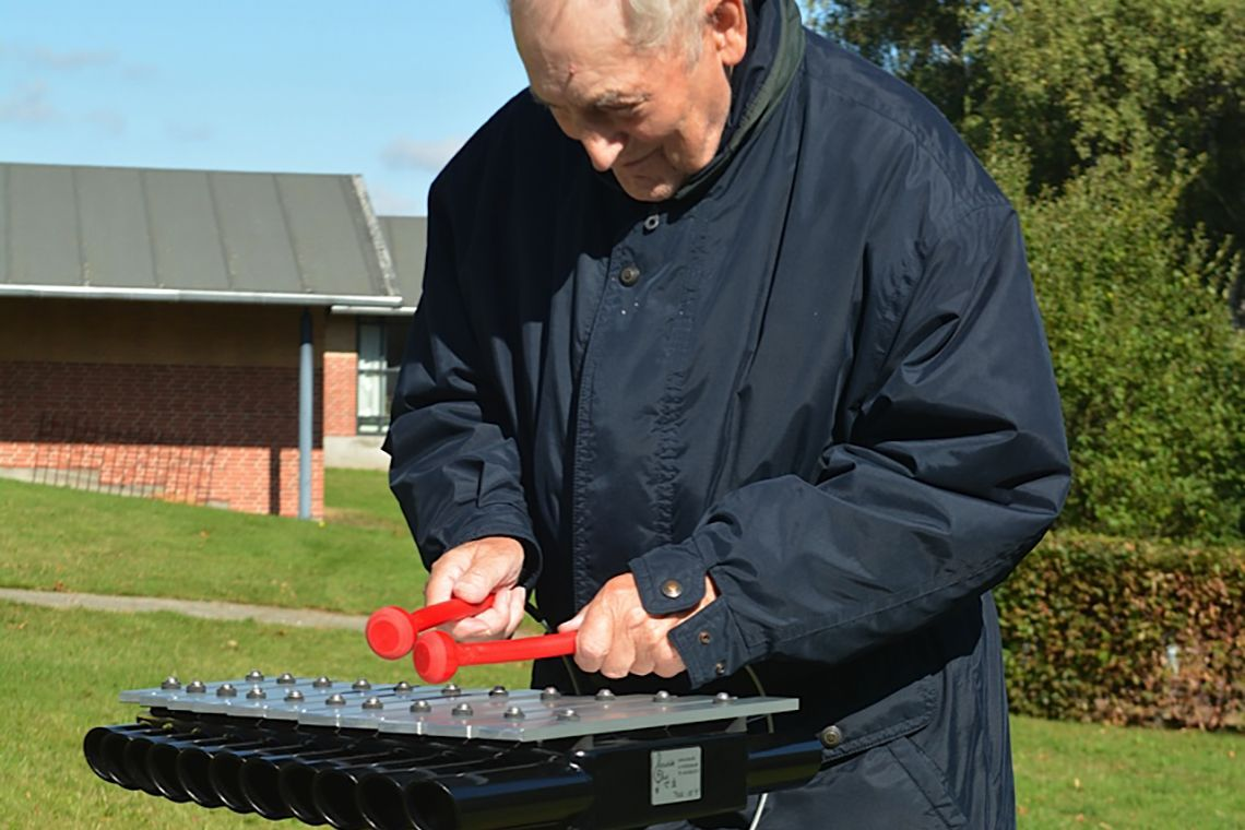 Older man playing an outdoor xylophone in care home garden