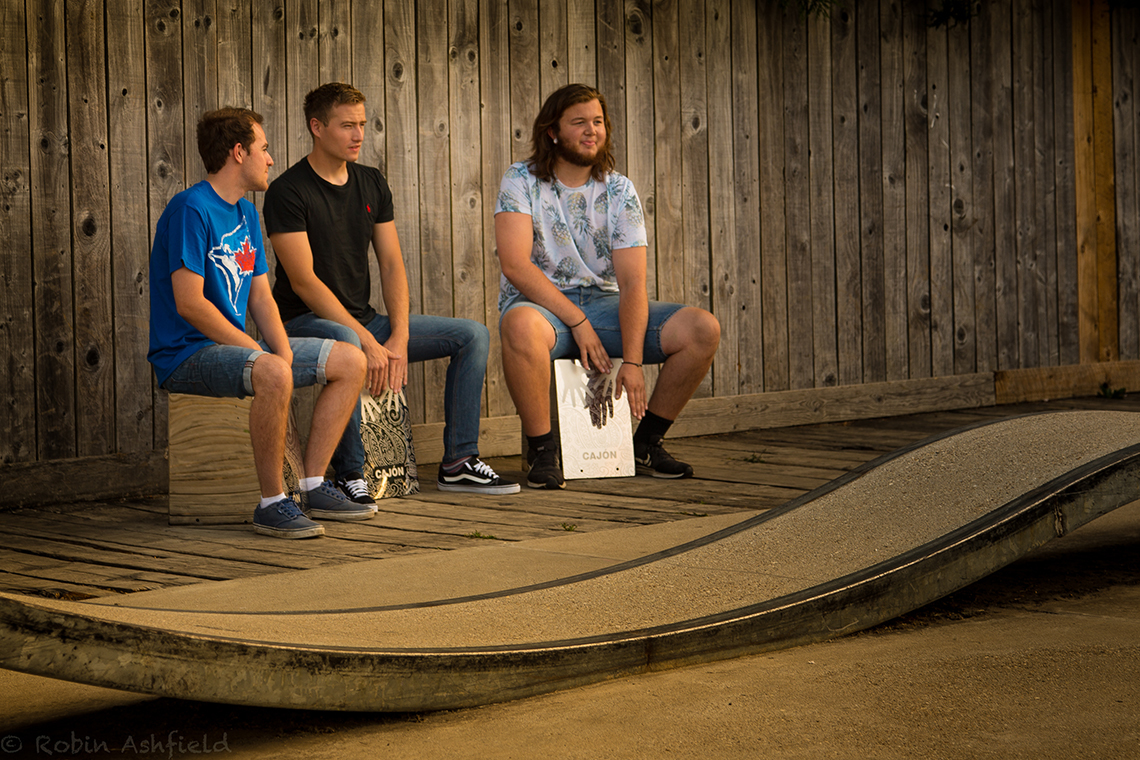 three young men sitting on stainless steel cajon percussion drums in an outdoor shelter