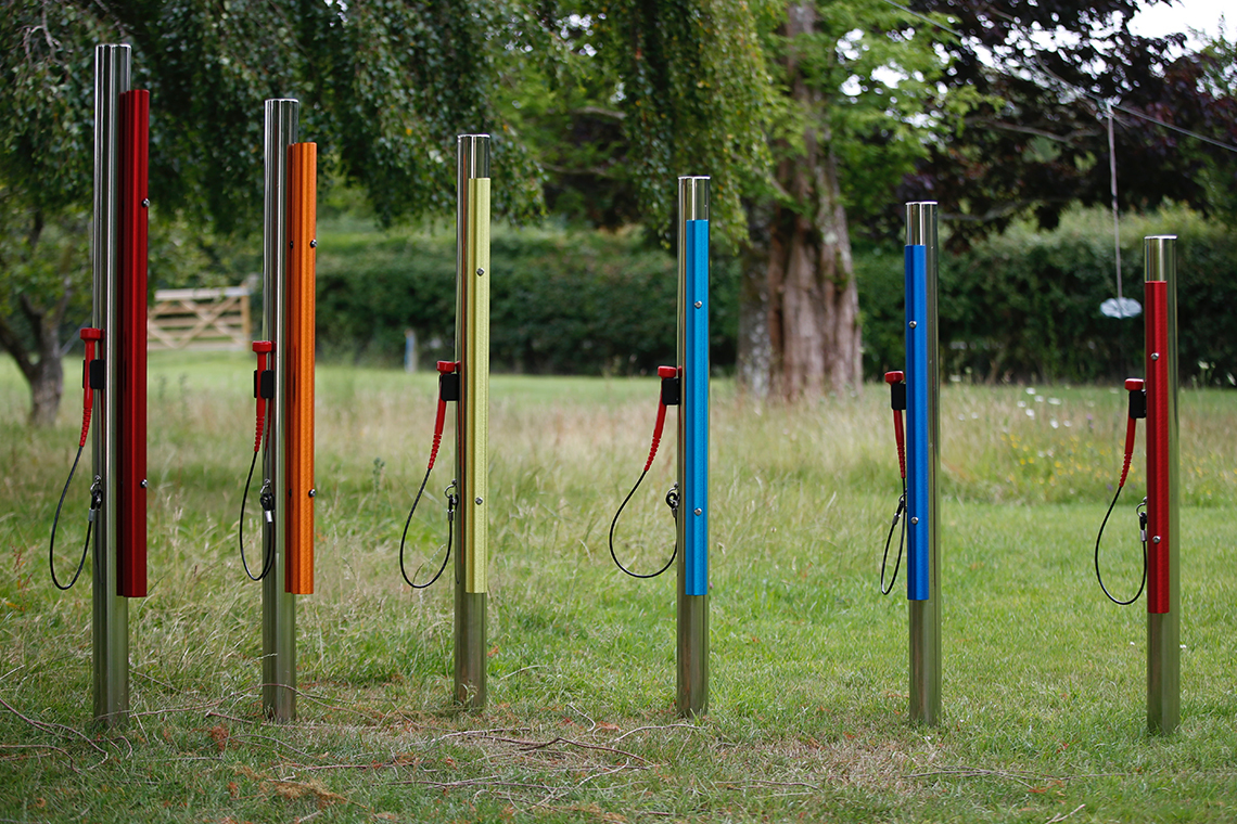 a set of six rainbow colored outdoor musical chimes on stainless steel posts with mallets