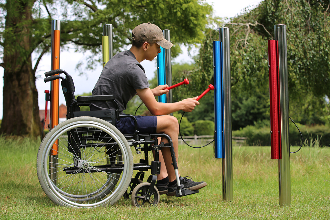 a young teenage boy in a wheelchair playing rainbow colored Calypson Chimes in a musical playground