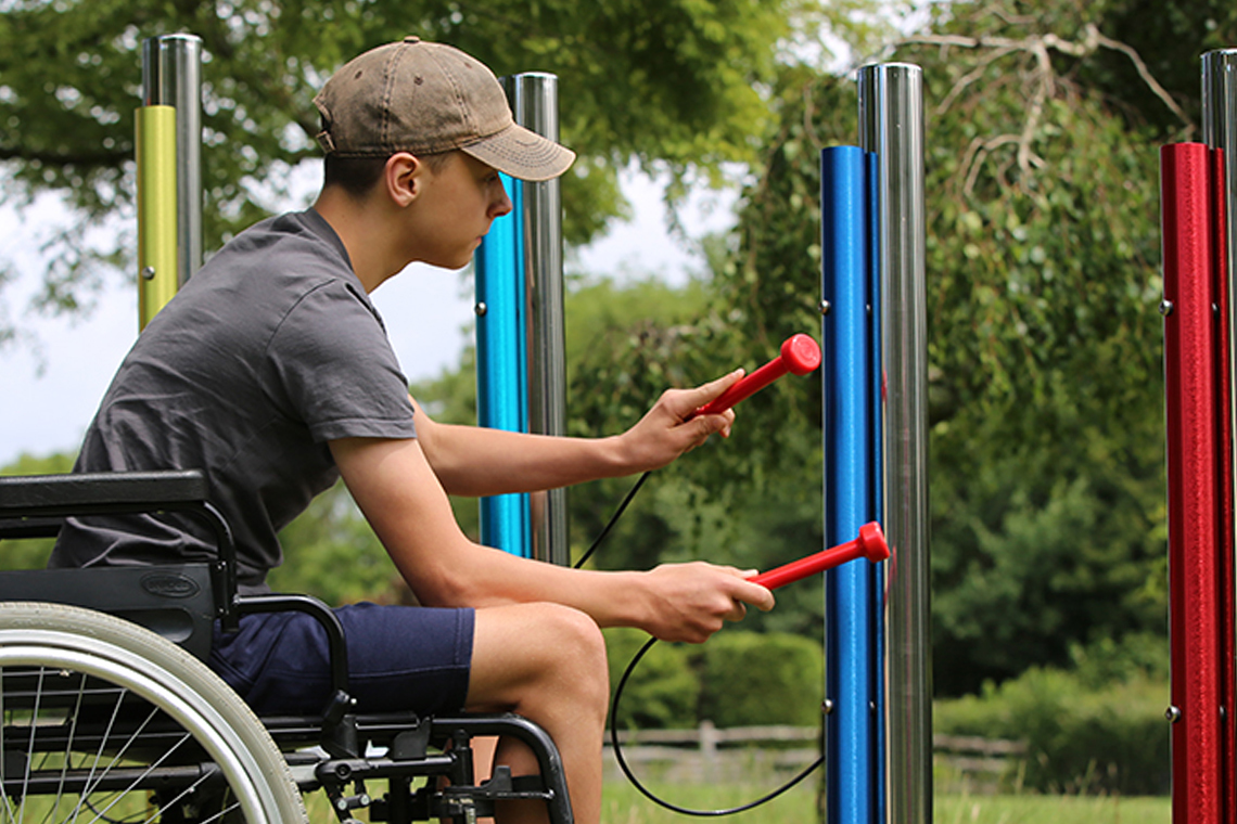 a young man in a wheelchair playing on rainbow colored outdoor musical chimes