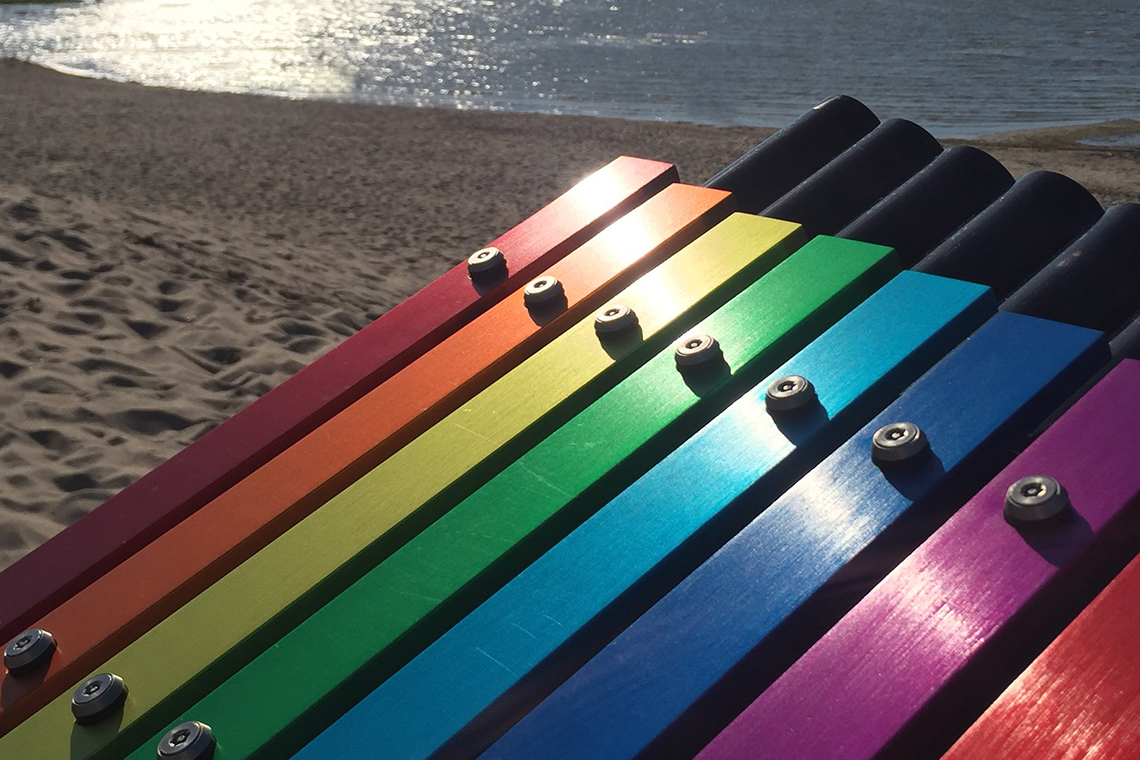 rainbow colored musical notes on an outdoor xylophone with a beach in the background
