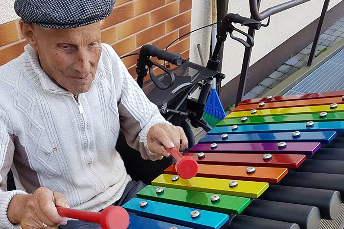Older man in cap playing an outdoor xylophone wit rainbow notes