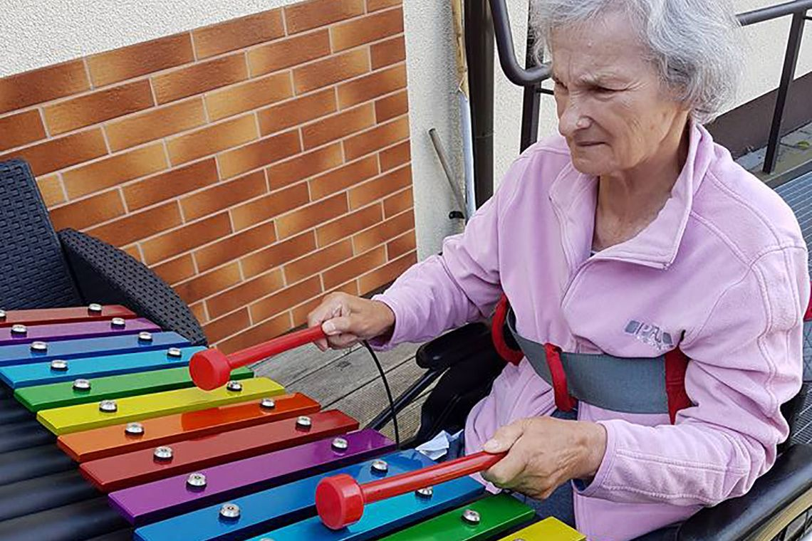 Older lady in a wheelchair playing colourful xylophone