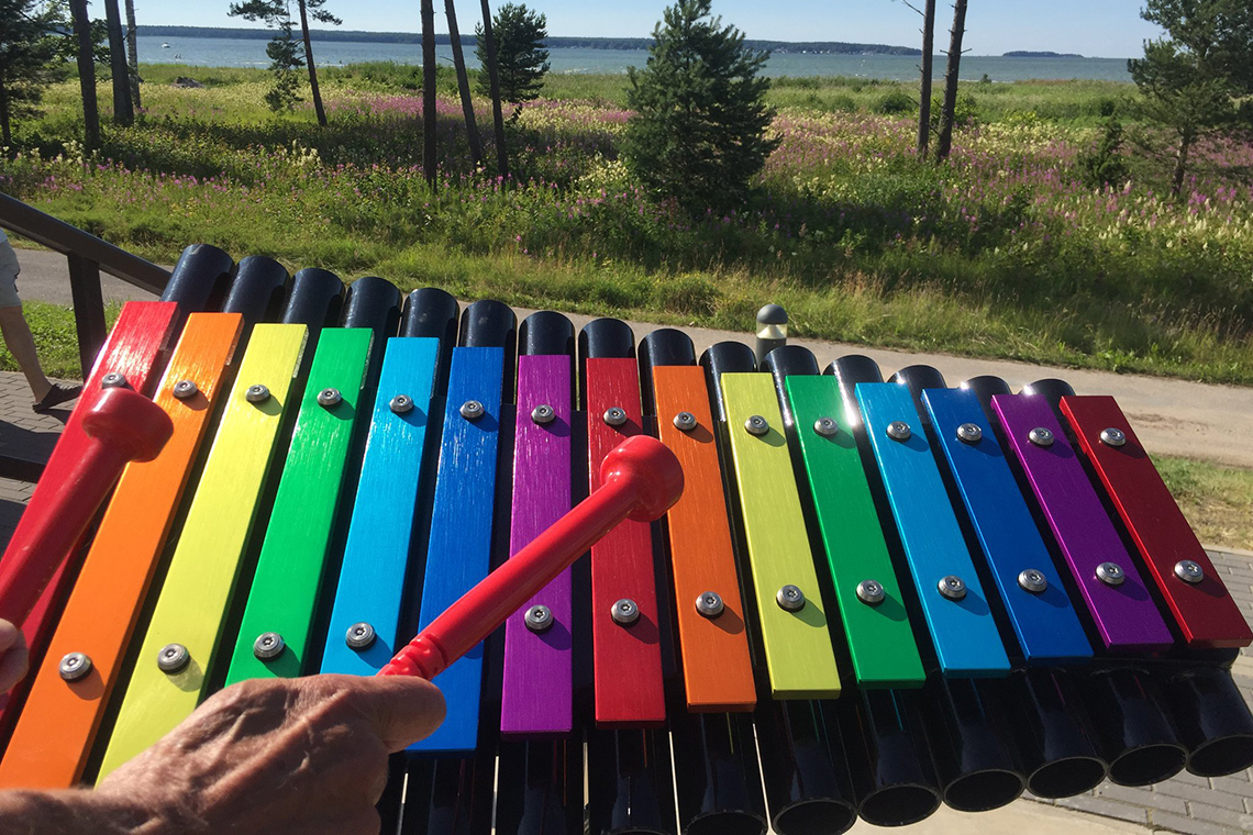 rainbow colored musical notes on an outdoor xylophone with a trees and the sea in the background